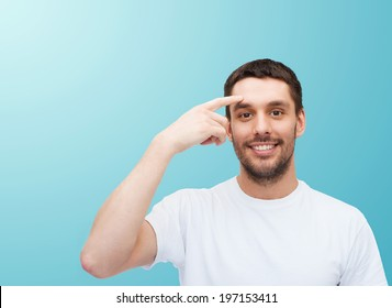 health and beauty concept - smiling young handsome man pointing to forehead
