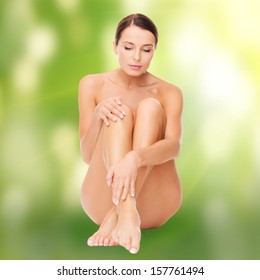 health and beauty, eco, bio, nature concept - beautiful naked woman touching her legs