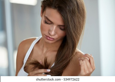 Health And Beauty. Portrait Of Beautiful Sad Young Woman With Long Hair In Hand. Closeup Of Unhappy Female Model Looking At Split Ended Hair. Hair Care Concept. High Resolution Image