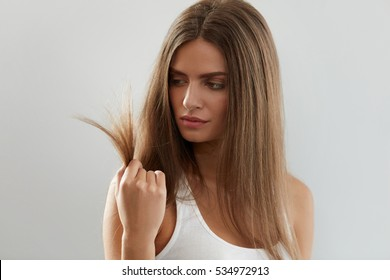 Health And Beauty. Portrait Of Beautiful Sad Young Woman With Long Hair In Hand. Closeup Of Unhappy Female Model Looking At Split Ended Hair On White Background. Hair Care Concept. High Resolution