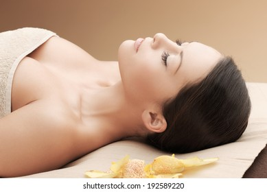 health and beauty, resort and relaxation concept - asian woman in spa salon lying on the massage desk