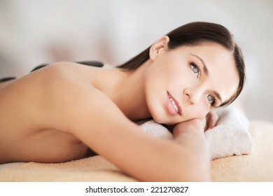 health and beauty, resort and relaxation concept - beautiful woman in spa salon with hot stones