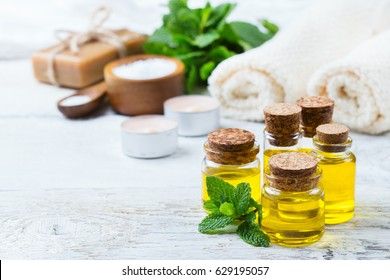 Health and beauty, still life spa concept. Assortment of organic essential oil in a small glass jar with green mint leaves towels sea salt candles on a white rustic wooden table