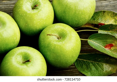 Health Benefits Of Green Apples. Green apples with leaf  on wooden background.
