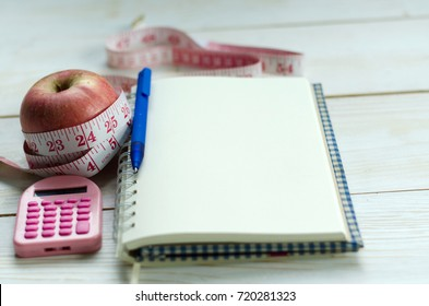 health and body slimming fitness concept. opened notebook, pen, red apples, calculator and measuring tape on white wooden table