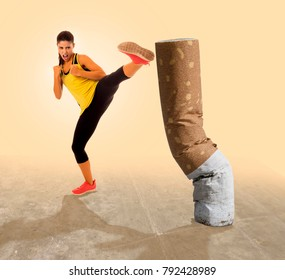 health care advertising campaign composite with young beautiful and furious girl in karate kick to huge cigarette butt in anti and stop smoking concept and quit tobacco addiction for healthy lifestyle