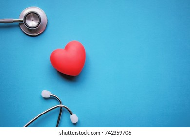 Health care check-up with red heart and Stethoscope on a blue background. Healing care concept and copy space. Above view of medical equipment for disease treatment on the blue backdrop.