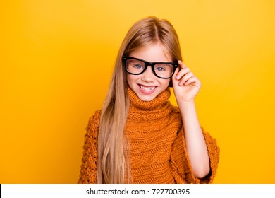 Health care, clear vision, specs, lenses pre teens concept. Close up portrait of charming blonde schoolgirl in fashionable black frames, knitted handmade warm outfit, intelligent and smiley