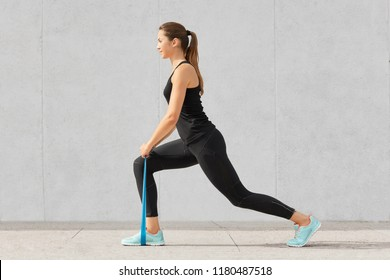 Health care concept. Beautiful woman with healthy skin, pony tail, has exercises with elastic band, dressed in sportsclothes, poses against grey background. Athletic sportswoman trains legs indoor