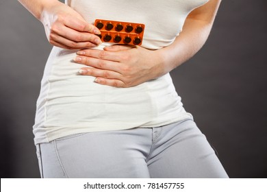 Health care concept. Bellyache, indigestion or food poisoning. Young female suffering from strong stomach ache abdominal pain, holding medical tablets activated carbon in hand