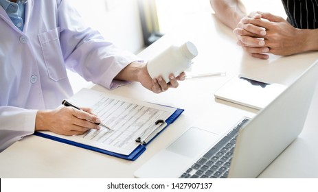 health care concept, doctor give a medicine bottle of drugs pills and explain the direction to use to patient in the hospital.