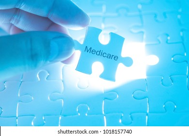Health Care Concept. Doctor holding a jigsaw puzzle with medicare word.