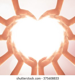 Health care concept: Human hands in shape of heart on blurred natural background