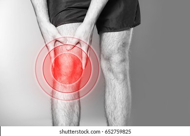 Health care concept. Man suffering from pain in knee on gray background