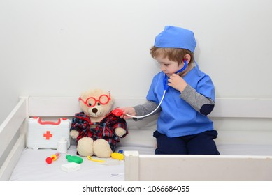 Health care concept. Medical examination of ill teddy bear in bed. White teddy bear in pediatrician's office. Cute kid boy playing doctor with plush toy at home. Game and play, hospital for children