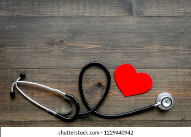 Health care concept. Stethoscope near heart sign on dark wooden background top view copy space