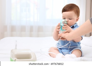 Health care concept. Woman with little baby and nebulizer indoors