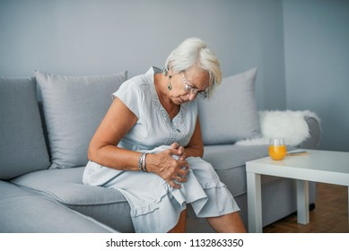 Health care concept. Woman suffering from pain in knee, closeup. Old age, health problem and people concept - senior woman suffering from pain in leg at home
