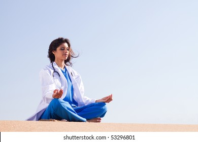 health care concept: young female doctor doing meditation on beach
