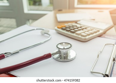 Health care costs concept picture :  Stethoscope  and calculator on a medical chart ,symbol for health care costs or medical insurance