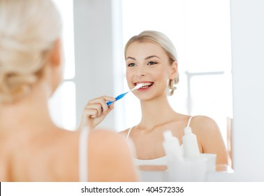 health care, dental hygiene, people and beauty concept - smiling young woman with toothbrush cleaning teeth and looking to mirror at home bathroom