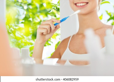 health care, dental hygiene, people and beauty concept - close up of smiling young woman with toothbrush cleaning teeth and looking to mirror at home bathroom over green natural background