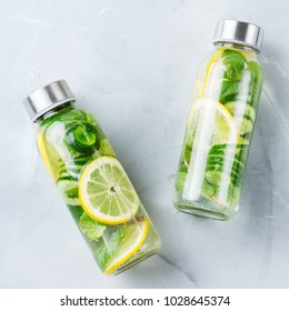 Health care, fitness, healthy nutrition diet concept. Fresh cool lemon cucumber mint infused water, cocktail, detox drink, lemonade in a glass jar. Light top view flat lay background