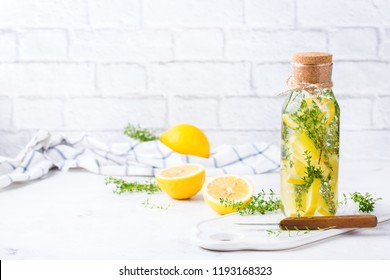 Health care, fitness, healthy nutrition diet concept. Fresh cool lemon thyme infused water, cocktail, detox drink, lemonade in a glass jar for spring summer days. Light kitchen copy space background