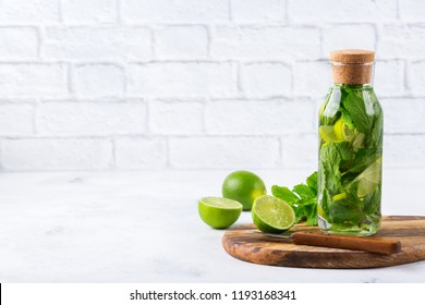 Health care, fitness, healthy nutrition diet concept. Fresh cool lemon lime mint infused water, cocktail, detox drink, lemonade in a glass jar for spring summer days. Light copy space background