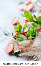 Health care, fitness, healthy nutrition concept. Fresh cool cucumber strawberry mint infused water, cocktail, detox drink, lemonade for spring summer days