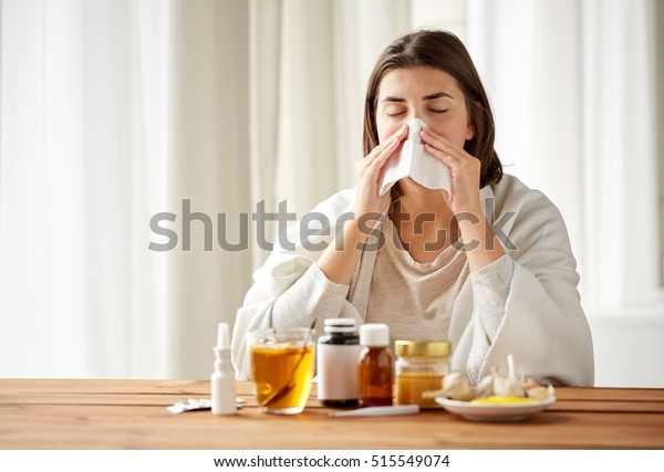 health care, flu, hygiene, age and people concept - sick woman with medicine blowing nose to paper wipe at home