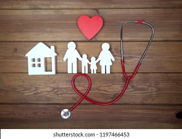 Health care and insurance concept. Family medicine. Icon of family, red heart, house and stethoscope on wooden background. Life insurance for whole family