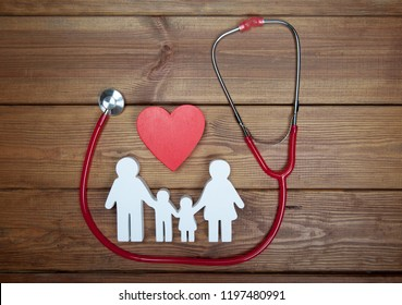 Health care and insurance concept. Family medicine. Icon of family, red heart and stethoscope on wooden background. Life insurance for whole family.