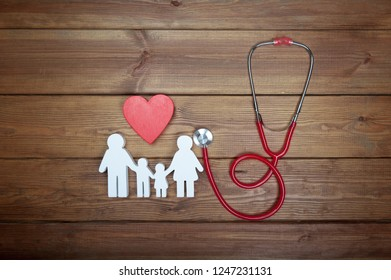 Health care and insurance concept. Family medicine. Icon of family, red heart and stethoscope or phonendoscope, on wooden background. Life insurance for whole family.