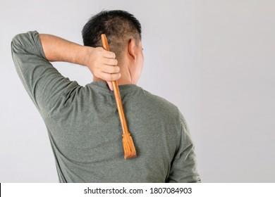 Gesundheitswesen oder Itschi oder Tinea Cruris Konzept: Porträt von Menschen, die Scratching Holz Stock auf Scratch auf der Rückseite. Studioaufnahme auf grauem Hintergrund