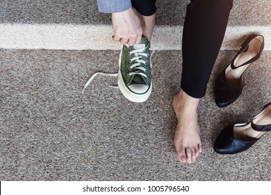 Health Care or Life Balance concept. Barefoot Business Woman sitting at stair to Changing Shoes from High Heel to Comfortable Sneaker. Top View