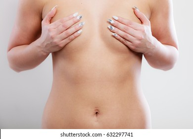 Health care medical concept. Close up young woman examining her breasts for lumps or signs of breast cancer