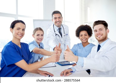 health care, medical education, people and medicine concept - group of happy doctors or interns with mentor meeting and showing thumbs up gesture at hospital