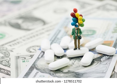 Health care and medical industry business concept, miniature people man holding balloons standing on white tablet pills on US dollar banknotes, success in medical research announcement.