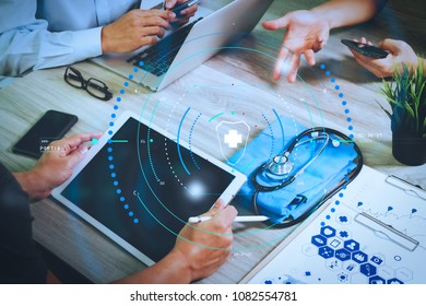 Health care and medical services with circular AR diagram.top view of Medicine doctor hand working with modern computer and digital pro tablet with his team on wooden desk.