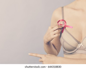 Health care, medicine and breast cancer awareness concept. Woman in bra with pink ribbon symbol pointing with finger to copy space, on blue
