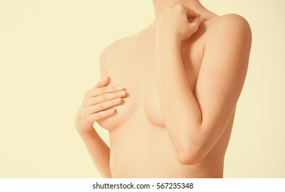 Health care, medicine, female controlling for cancer. Young topless woman covering her breast with hands