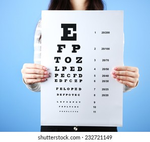 Health care, medicine and vision concept - woman with eye chart