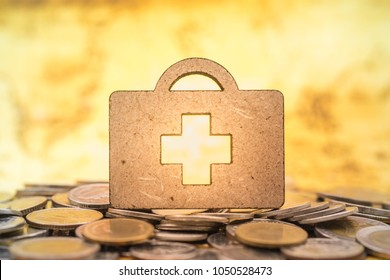 Health Care and money concept. Close up of wooden bag shape with red cross symbol on pile od coins.