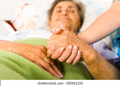 Health care nurse holding elderly lady's hand with caring attitude.