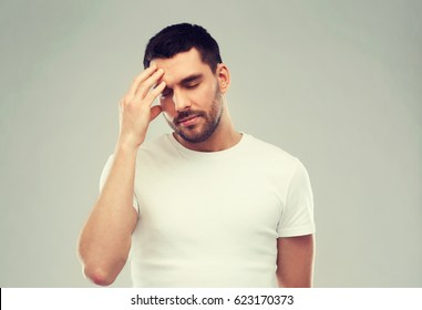 health care, pain, stress and people concept - young man suffering from headache