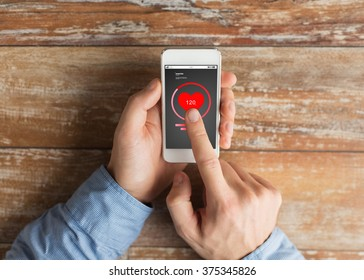 health care, people and technology concept - close up of male hands holding smartphone and pointing finger heart- rate icon on screen