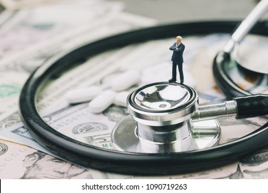Health care, pharmaceutical and medical industry business concept, miniature businessman standing on stethoscope and white tablet pills on US dollar banknotes.