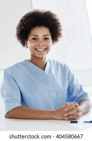 health care, profession, people and medicine concept - happy female african american doctor or nurse with clipboard at hospital