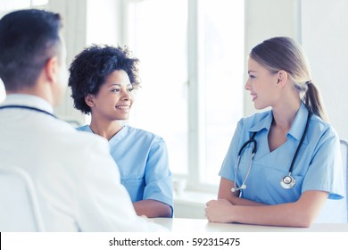 health care, profession, people and medicine concept - group of happy doctors or nurses meeting and talking at hospital